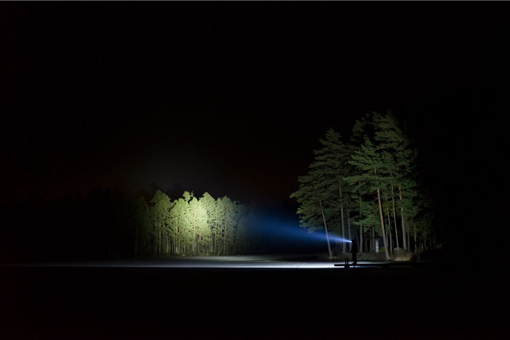 A man holding a flashlight outside forest during night