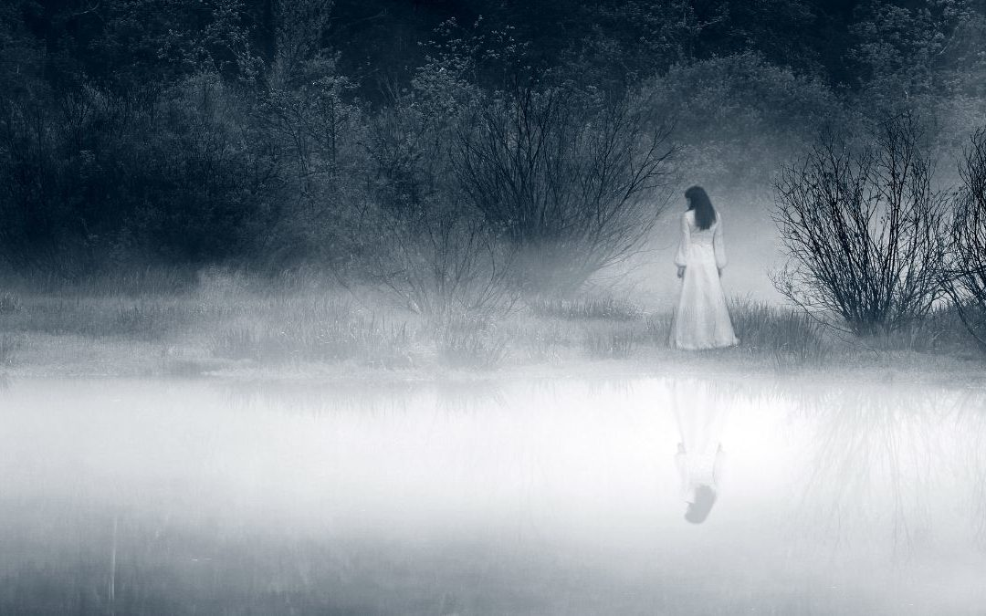 Haunting woman in white standing by a thick mist