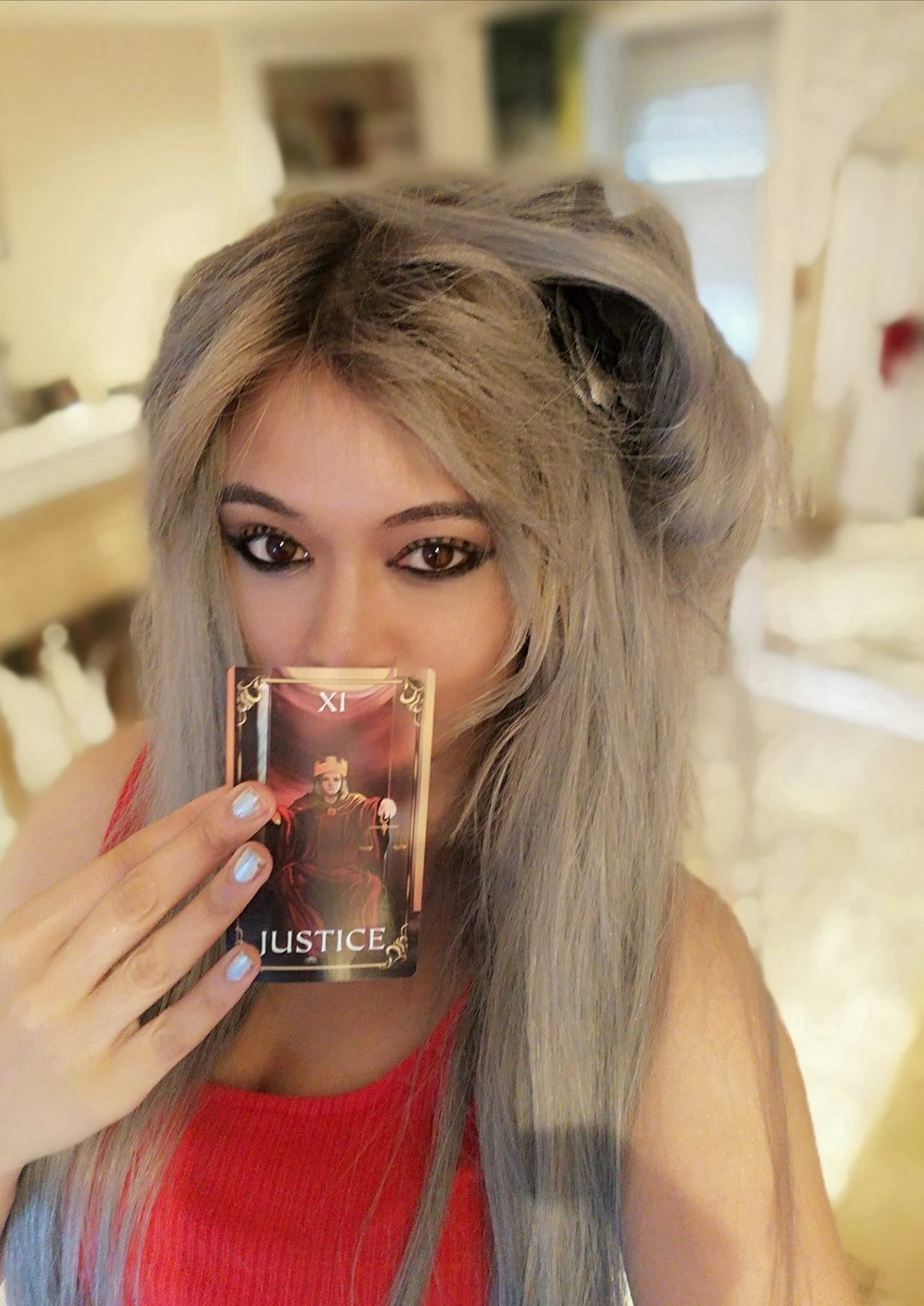 Sarah Brownlee holding justice tarot card