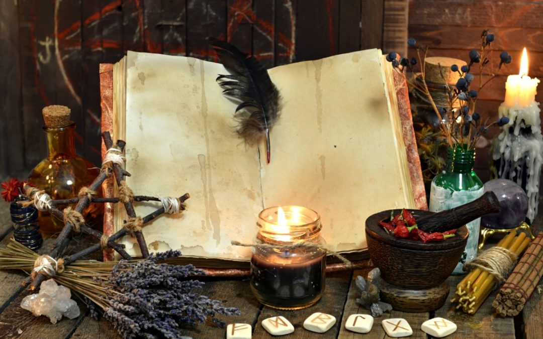 Magic book for witchcraft surrounded by items like lavender, stones, mortal bowl etc.