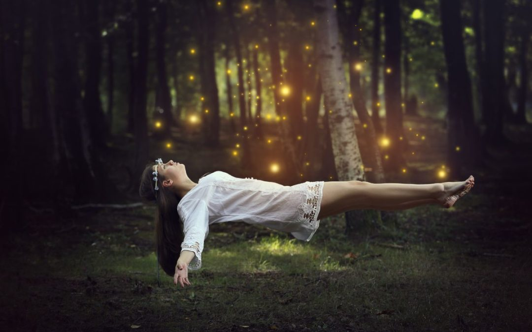 Woman hovering over grass in forest