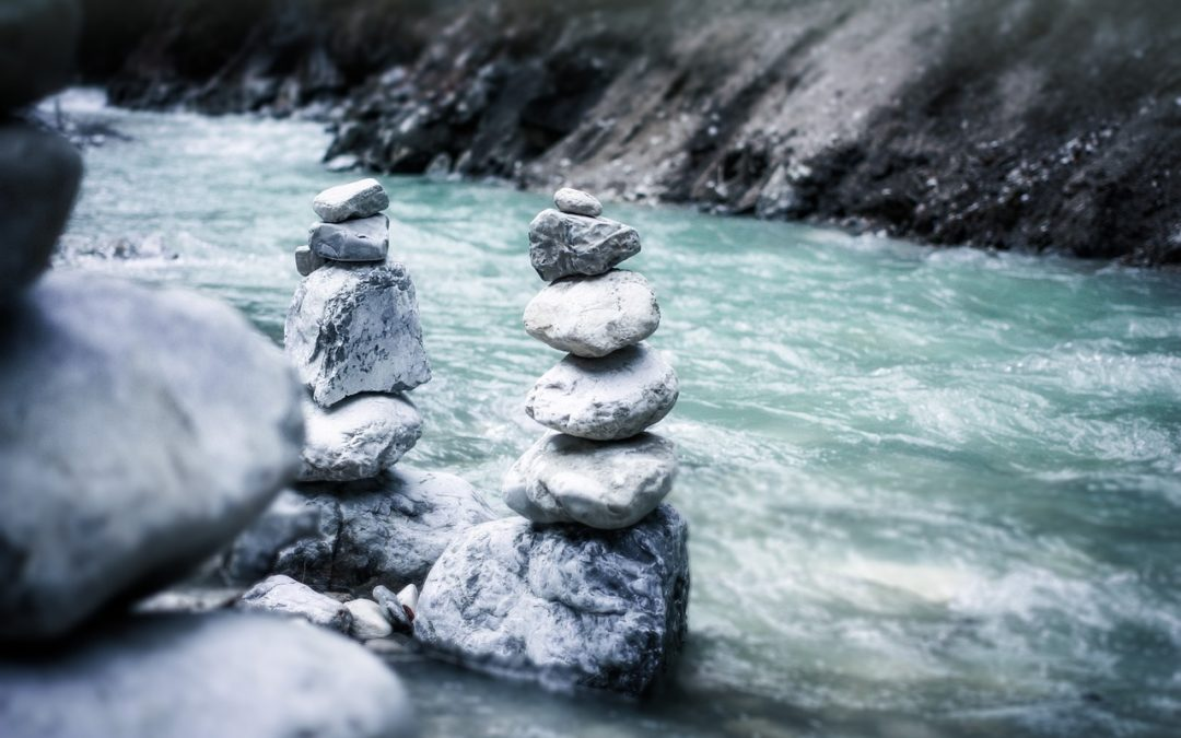 Cairn stones besides a flowing river