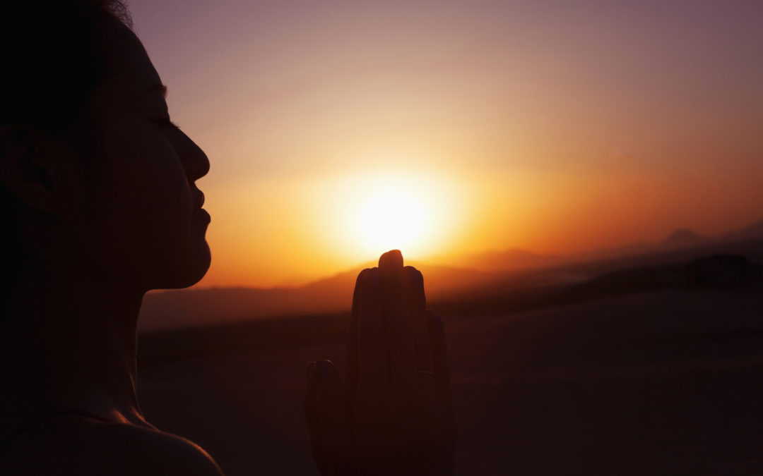 Woman with hands together in prayer pose during a sunset