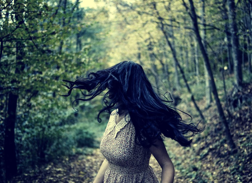 Young woman running scared in forest